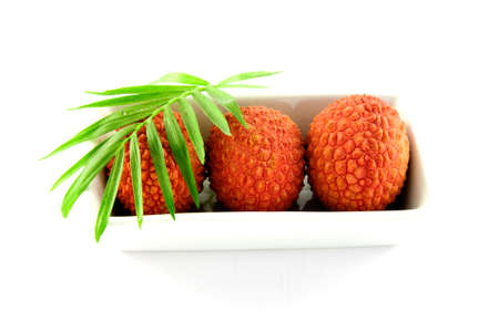 litschi: Three lychee and a green leaf in a dish