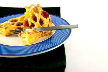 Raspberry and custard danish on a blue and white plate with a fork and black napkin on a white background photo