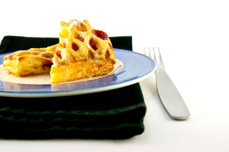 danish puff pastry: Raspberry and custard danish on a blue and white plate with a fork and black napkin on a white background