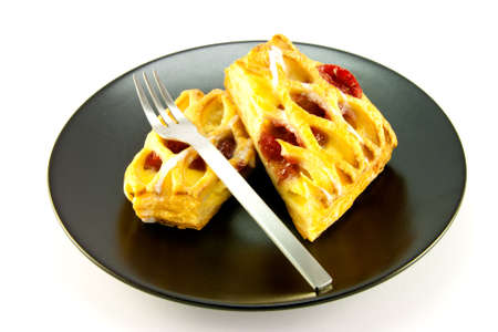 Raspberry and custard danish on a black plate with a fork on a white background photo