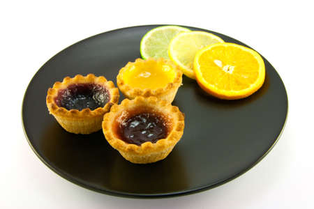 jam tarts: Red and yellow small jam tarts with slices of lemon, lime, and orange on a black plate on a white background Stock Photo