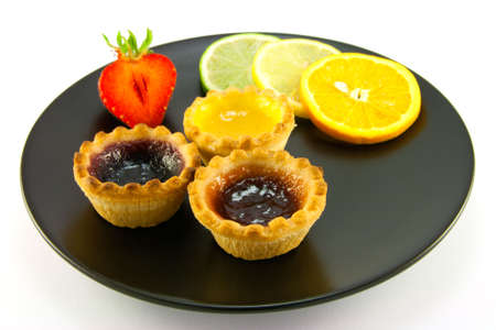 jam tarts: Red and yellow small jam tarts with slices of lemon, lime, orange and strawberry on a black plate on a white background