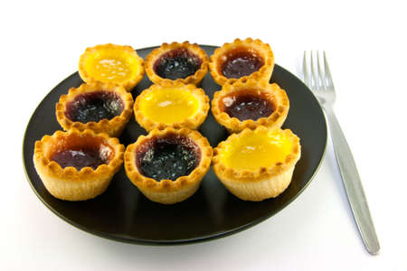 jam tarts: Selection red and yellow small jam tarts on a black plate with a fork on a white background