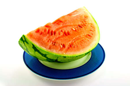 Slice of watermelon with green skin and red melon with seeds on a blue plate with a white background Stock Photo - 5255324