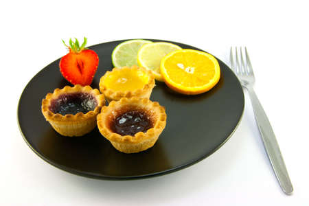 jam tarts: Red and yellow small jam tarts with slices of lemon, lime, orange and strawberry on a black plate with fork on a white background