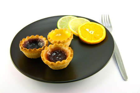 jam tarts: Red and yellow small jam tarts with slices of lemon, lime, and orange on a black plate with a fork on a white background Stock Photo