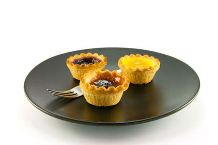 jam tarts: Three red and yellow small pastry jam tarts on a black plate with a fork on a white background