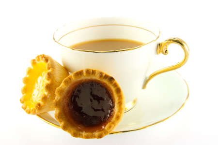 jam tarts: Tea in a cup and saucer with yellow and red jam tarts on a white background Stock Photo