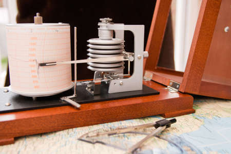 atmospheric pressure: Barograph in a wooden box with the lid open standing on a map