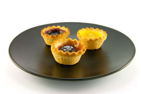 jam tarts: Three red and yellow small pastry jam tarts on a black plate with a white background Stock Photo
