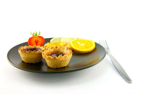jam tarts: Red and yellow small jam tarts with slices of lemon, lime, orange and strawberry on a black plate with fork on a white background  Stock Photo