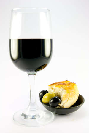 Glass of red wine with three green olives and crusty bread in a small black bowl on a plain background Stock Photo - 5333876