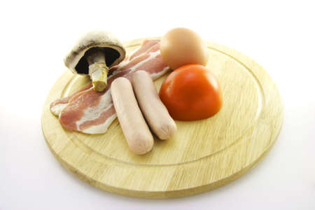 uncooked bacon: Uncooked sausage, bacon, mushroom, egg and tomato on a round plate with a white background Stock Photo