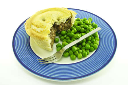meat pie: Small round meat pie with green peas on a round blue plate with a small fork on a white background
