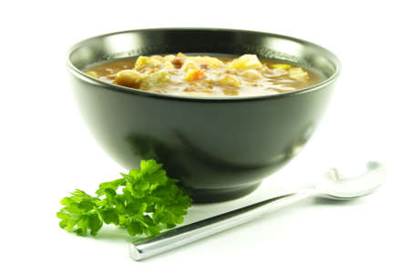 chunky: Hot chunky vegetable soup with a sprig of parsley and a spoon in a small black bowl on a white background Stock Photo