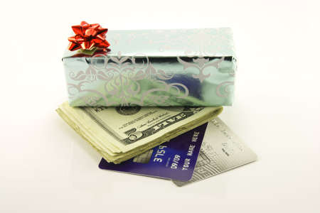 Single shiny silver gift with a red bow, dollars and plastic credit cards on a reflective white background Stock Photo - 5781372