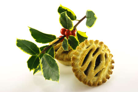mincemeat: Two small round sweet mince pies with a sprig of green and red holly on a reflective white background