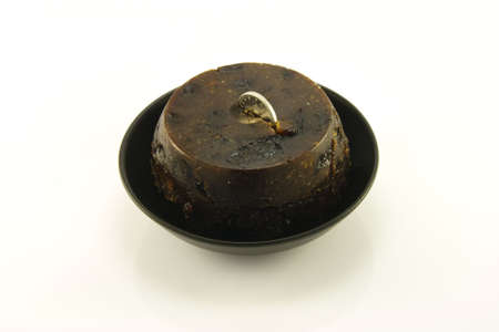 Single small christmas Pudding in a small black dish with a small silver coin in the top on a reflective white background photo