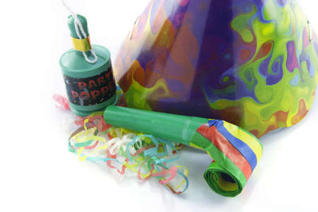 cone shaped: Bright cone shaped party hat and party popper with blower and party streamers on a reflective white background Stock Photo