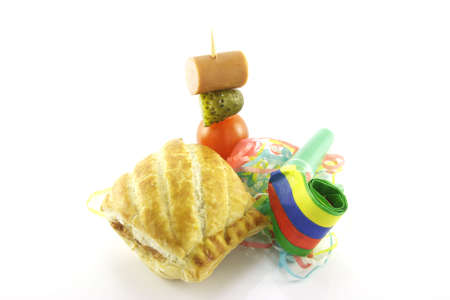 Small sausage roll with party blower and cocktail stick containing hot dog sauage, gherkin and tomato on a reflective white background photo