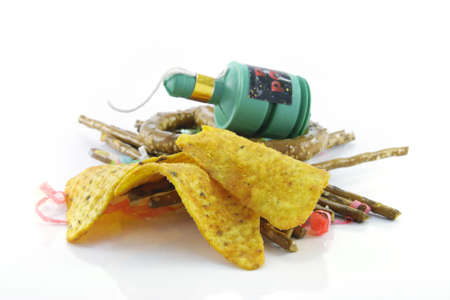 Salty brown tasty pretzels and crispy nachos with party blower and streamers on a reflective white background photo