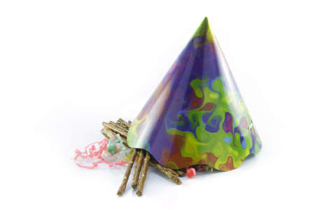 cone shaped: Salty brown tasty pretzels with cone shaped party hat and streamers on a reflective white background