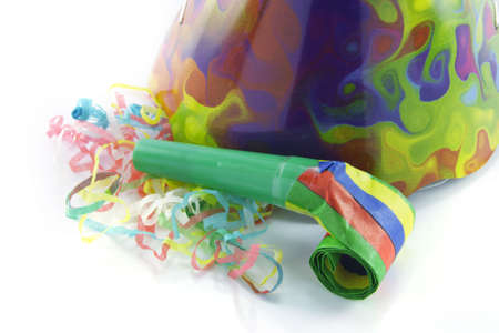 cone shaped: Bright cone shaped party hat and blower with party streamers on a reflective white background