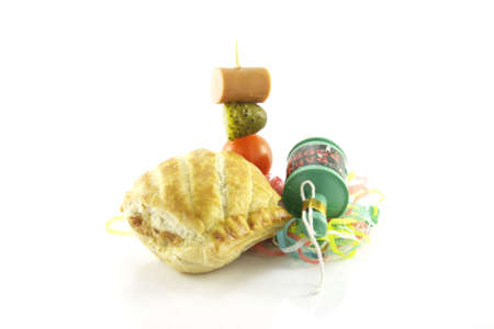 Small sausage roll with party popper and cocktail stick containing hot dog sausage, gherkin and tomato with streamers on a reflective white background photo