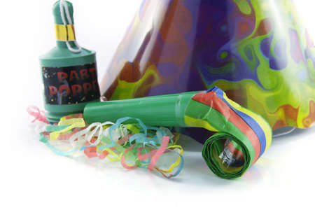 party popper: Bright cone shaped party hat and party popper with blower and party streamers on a reflective white background Stock Photo