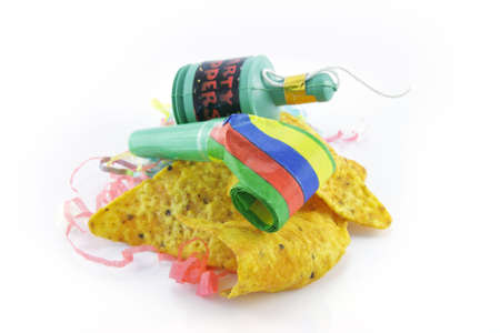 Baked spicy nachos with party blower and popper and party streamers on a reflective white background photo