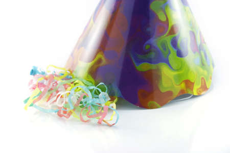 cone shaped: Bright cone shaped party hat with party streamers on a reflective white background