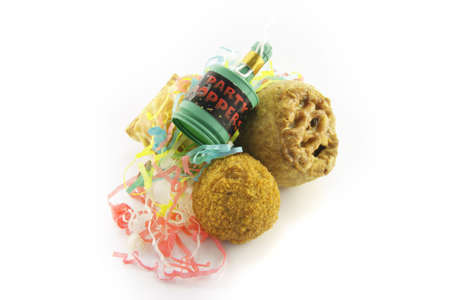 Small tasty pork pie, small round scotch egg and streamers with party popper on a reflective white background photo