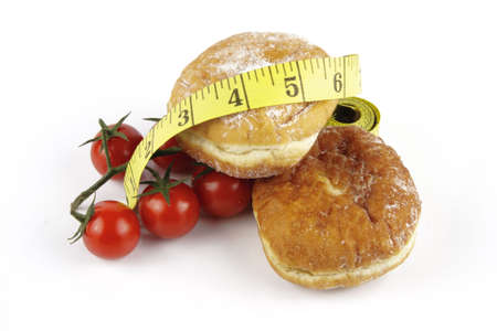 Contradiction between healthy food and junk food using red ripe tomatoes and doughnuts with a yellow tape measure on a reflective white background  photo