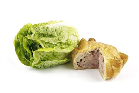 Contradiction between healthy food and junk food using a green salad lettace and pork pie on a reflective white background  photo