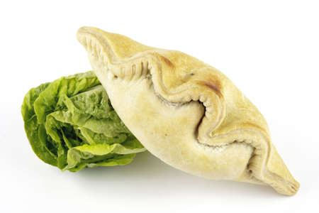 Contradiction between healthy food and junk food using a green salad lettace and pasty on a reflective white background  photo