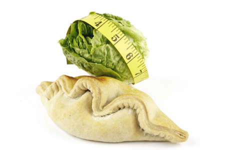 Contradiction between healthy food and junk food using a green salad lettace and pasty with a yellow tape measure on a reflective white background  photo