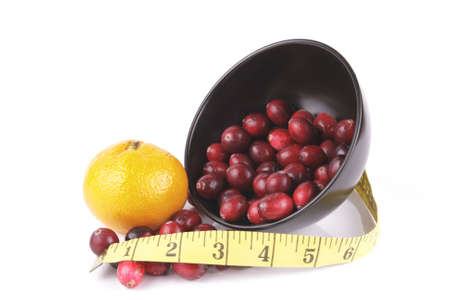 satsuma: Red ripe cranberries spilling out of a small round black bowl on its side with a tape measure and satsuma on a reflective white background