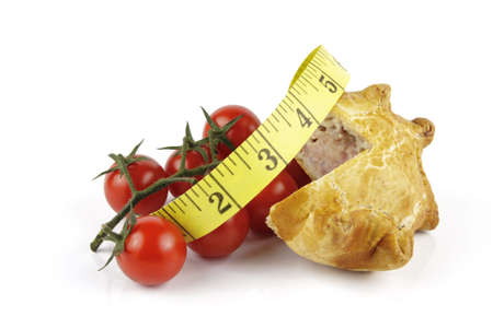 Contradiction between healthy food and junk food using tomatoes and a pork pie with a tape measure on a reflective white background  photo