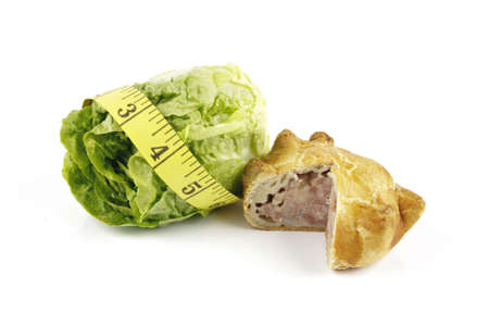 Contradiction between healthy food and junk food using a green salad lettace and pork pie with a yellow tape measure on a reflective white background  photo
