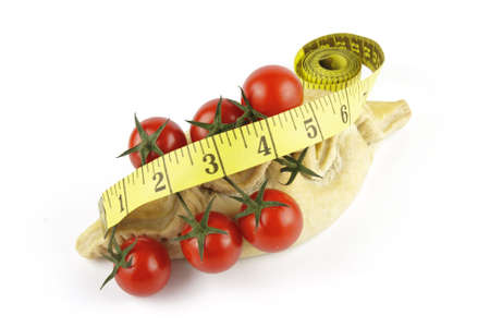 Contradiction between healthy food and junk food using tomatoes and a pasty with a tape measure on a reflective white background  photo