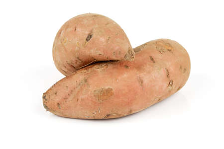 spud: Two raw unpeeled sweet potatoes on a reflective white background