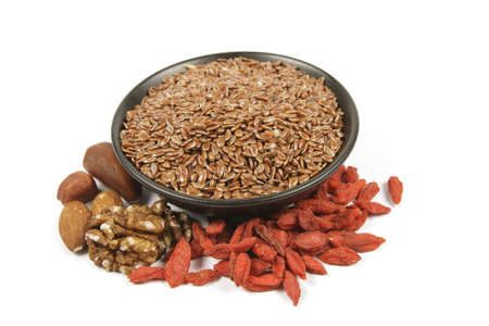 linseed: Brown linseed seeds in a small black bowl with mixed nuts and goji berries on a reflective white background