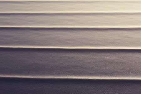implacable: les ondes cr��es sur une mer calme avec un soleil de soir�e r�tro-�clair� pour mettre en �vidence les mouvements