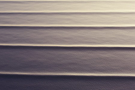 relentless: wave patterns created on a calm ocean with a backlit evening sun to highlight the movements