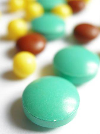 pilule: Amarillo verde y rojo p�ldoras sobre el Libro Blanco Foto de archivo