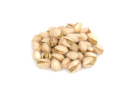Heap circle of roasted Pistachio nuts isolated on white background