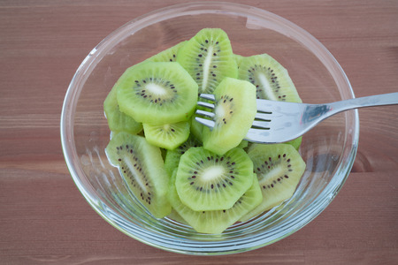 Bowl full with high in vitamins Kiwi fruit slices and fork isolated on wooden background