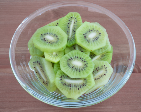 Bowl full with high in vitamins Kiwi fruit slices isolated on wooden background
