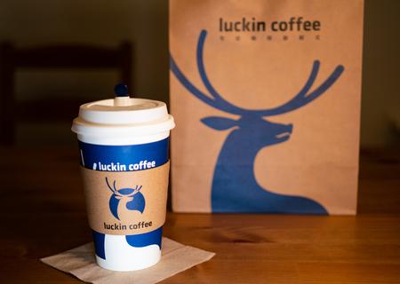 1 de septiembre de 2018, Wuhan China: una taza de café con funda de café Luckin sobre fondo de mesa de madera