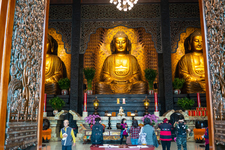 22 February 2018, Kaohsiung Taiwan: Three Buddha and people praying at Main shrine of Sangha Fo Guang Shan Monastery in Kaohsiung Taiwan